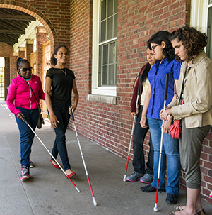 A group of high school students standing outside against a brick wall with two students walking towards the group using white canes
