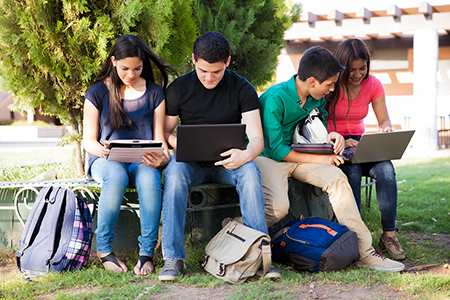 A group of students outside using smart devices and laptops at school