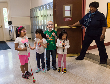 Four preschoolers standing in a hallway, some using a white cane, while the teacher holds open the door