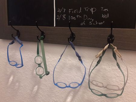Several pairs of glasses hanging from hooks on a chalkboard