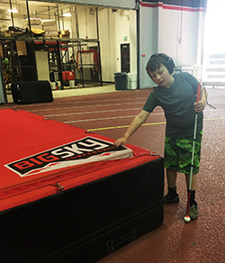 Eddie standing with his white cane touching a large gym mat