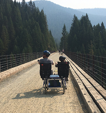 Eddie and his dad riding on a bike on the Hiawatha trail on the Montana/Idaho border with their backs to the camera