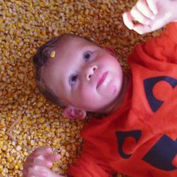 A little boy wearing a red shirt laying on his back looking up at the camera, playing with corn kernels