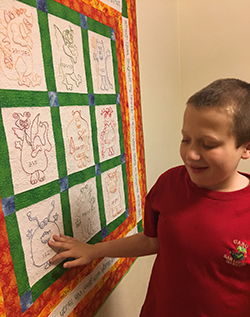 Eddie touching a picture quilt hanging on the wall