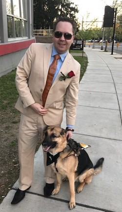 James Boehm standing on the sidewalk with his guide dog