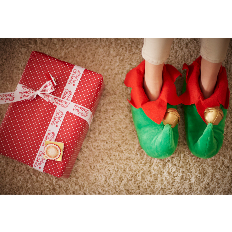 A top down view of a child wearing green and red elf shoes with bells on the toes