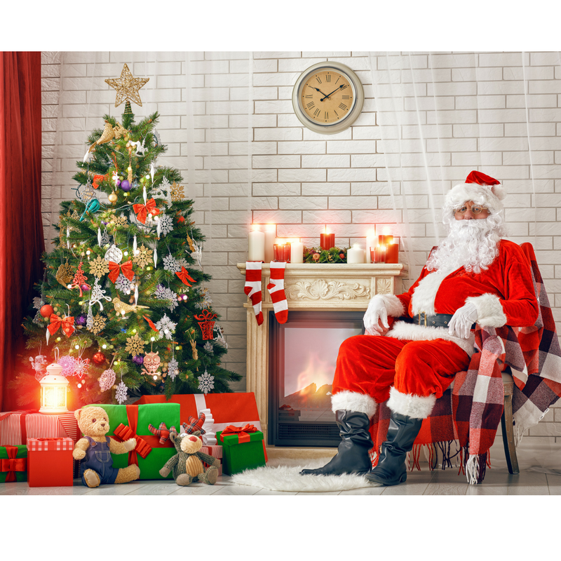 Santa sitting in a rocking chair next to a decorated Christmas tree with a fireplace in the background