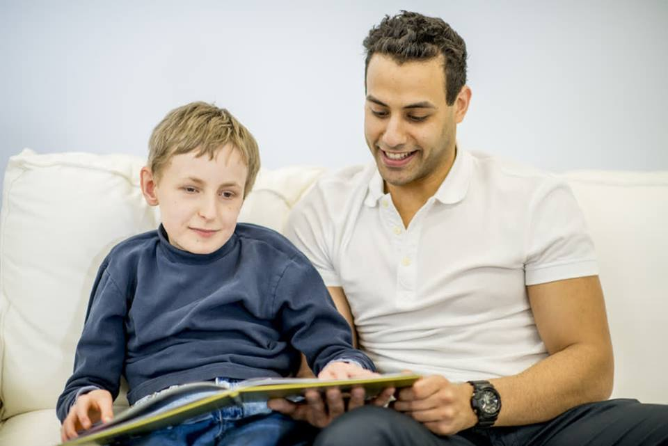 boy sitting on the couch with his father reading braille