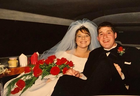 A young Emily Coleman in a wedding dress and her husband sitting in the back of a limo after their wedding