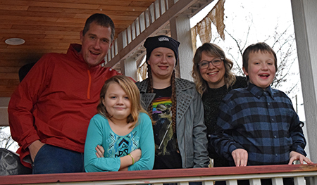 Emily Coleman with her husband and their three children, standing outside on a porch