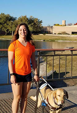 Letticia Martinez with her guide dog standing outside