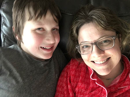 Emily Coleman and her son Eddie laying down together looking up and smiling at the camera