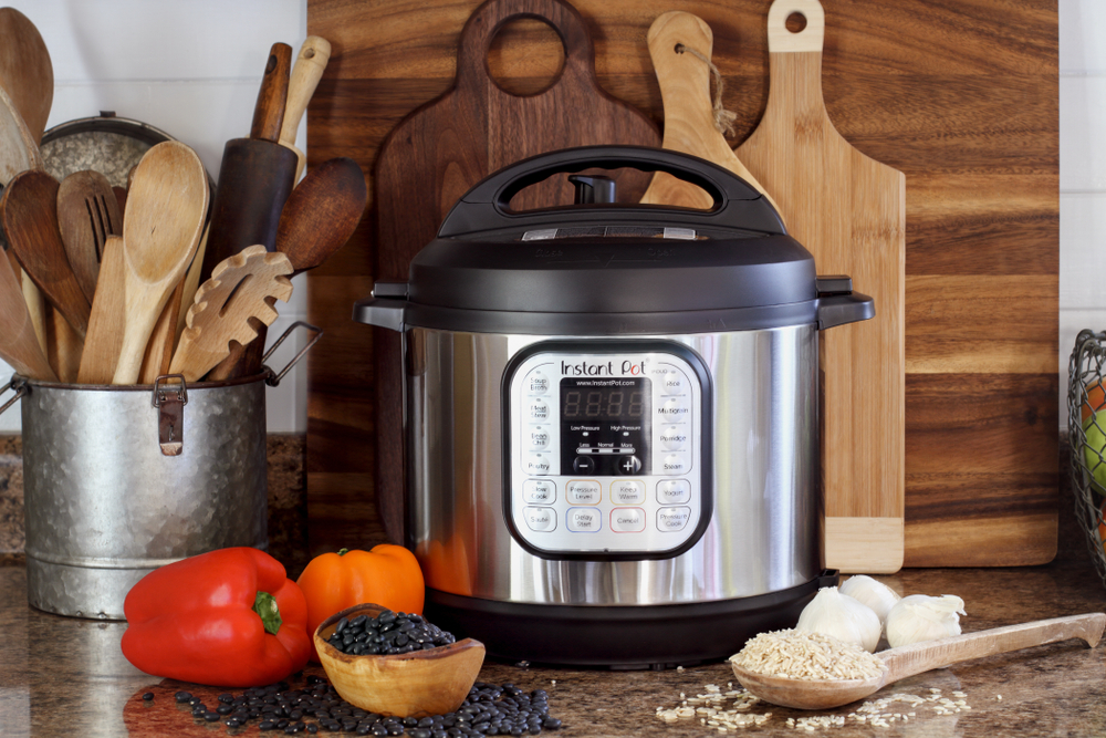 Instant Pot surrounded by various kitchen tools, cutting board