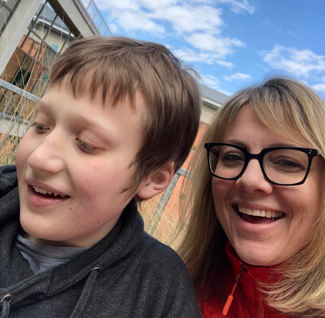 Blonde woman in glasses smiling with teenage son