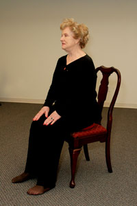an older woman sitting on an inflatable disk placed on a   chair