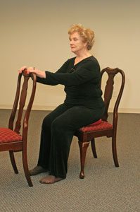 a seated woman holding on to the back of another chair in   front of her