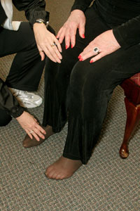close up of the hands of an exercise instructor helping a   seated woman place her feet 8 inches apart