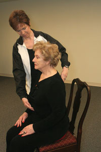 an exercise instructor helping a woman to sit up very   straight