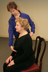 fitness trainer guiding a seated older woman to sit up straight