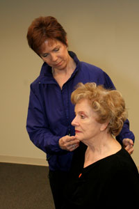 an exercise instructor helping a woman to tuck in her   chin