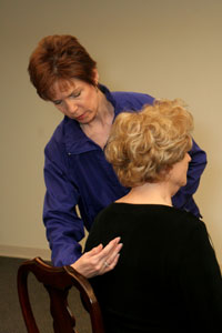 an exercise instructor helping a woman to pull her   shoulder blades together