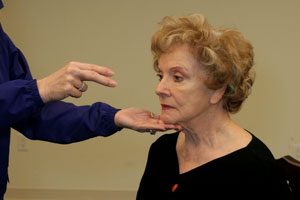 close up of the hand of an exercise instructor helping a   woman to keep her chin parallel to the ground