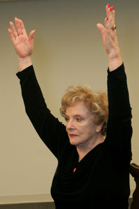 seated older woman holding her arms straight up