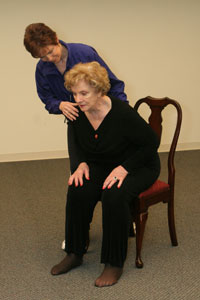 female exercise instructor helping an older seated woman   to bend forward