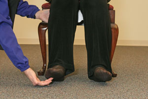 close up of the hand of an exercise instructor helping a   woman to raise her toes off the floor
