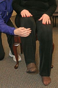 close up of the hand of an exercise instructor helping a   woman raise her knee in a marching motion