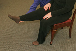 close up of the hand of an exercise instructor helping a   seated woman to lift her right leg straight out in front of her