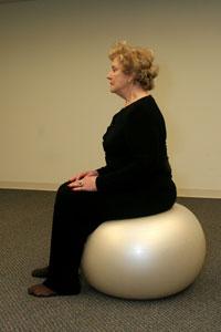 an older woman seated on a balance ball