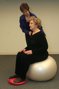 an exercise instructor positioning a woman seated on a   balance ball with her feet on an inflatable disk