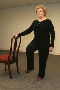 a woman holding on to a chair on her right side while she   raises her right foot off the ground