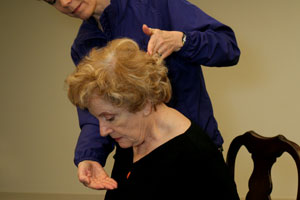 fitness trainer helping older woman lower chin properly for a neck stretch