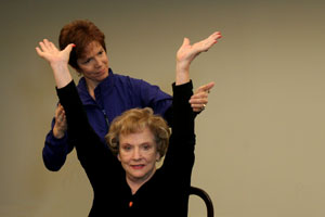 fitness trainer helping seated older woman raise her arms above her head