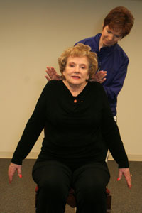 fitness trainer helping seated older woman raise her shoulders in a shoulder shrug stretch