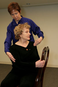 fitness trainer helping seated older woman rotate at the waist to her left