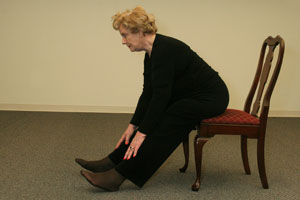 seated older woman bending forward at waist with her hands resting on legs just below knees