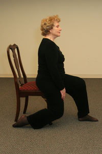 seated older woman sliding her right leg back with knee close to a 90-degree angle for a quadriceps stretch