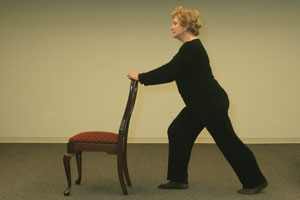 older woman standing behind chair with hands resting on chair back, right leg bent and left leg extended stretched straight out behind her, left foot on floor