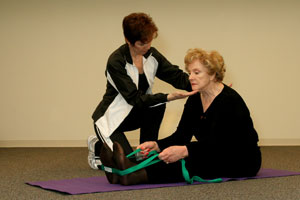 fitness trainer helping older woman seated on exercise mat to bend forward as she uses an exercise strap wrapped around her feet to stretch her hamstrings