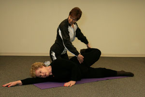 fitness trainer helping older woman laying on right side on floor lift and bend left leg back in a quadriceps stretch