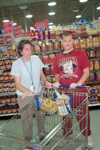 Joven empuja un carrito en el supermercado; su maestra está cerca de él