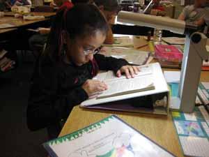 La chica se sienta en un escritorio, y utiliza un cuaderno y iluminación extra