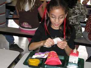 Elizabeth in the school cafeteria opening her plastic ware