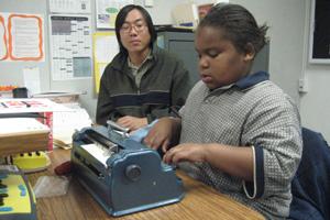 Levon escribe en braille mientras un auxiliar lo observa