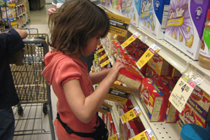 Rachel saca palomitas de maíz de un estante del supermercado