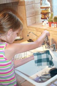 la chica que consigue una tela mojó en fregadero
