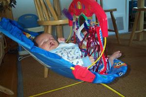 beb&eacute en una silla con una barra de juguetes